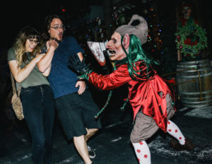 Two people being scared by someone in a scary elf costume holding a bloody axe.