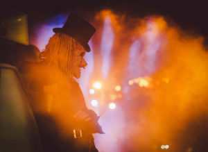 Zombie with a top hat leaning against a car at night.