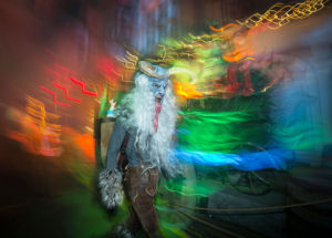 A blurry image of a person in a blue animal costume with white horns.