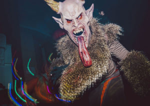 A person in a devil costume with horns and a long tongue.