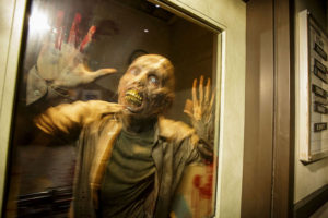 A zombie covered in blood pushed up against a glass door.